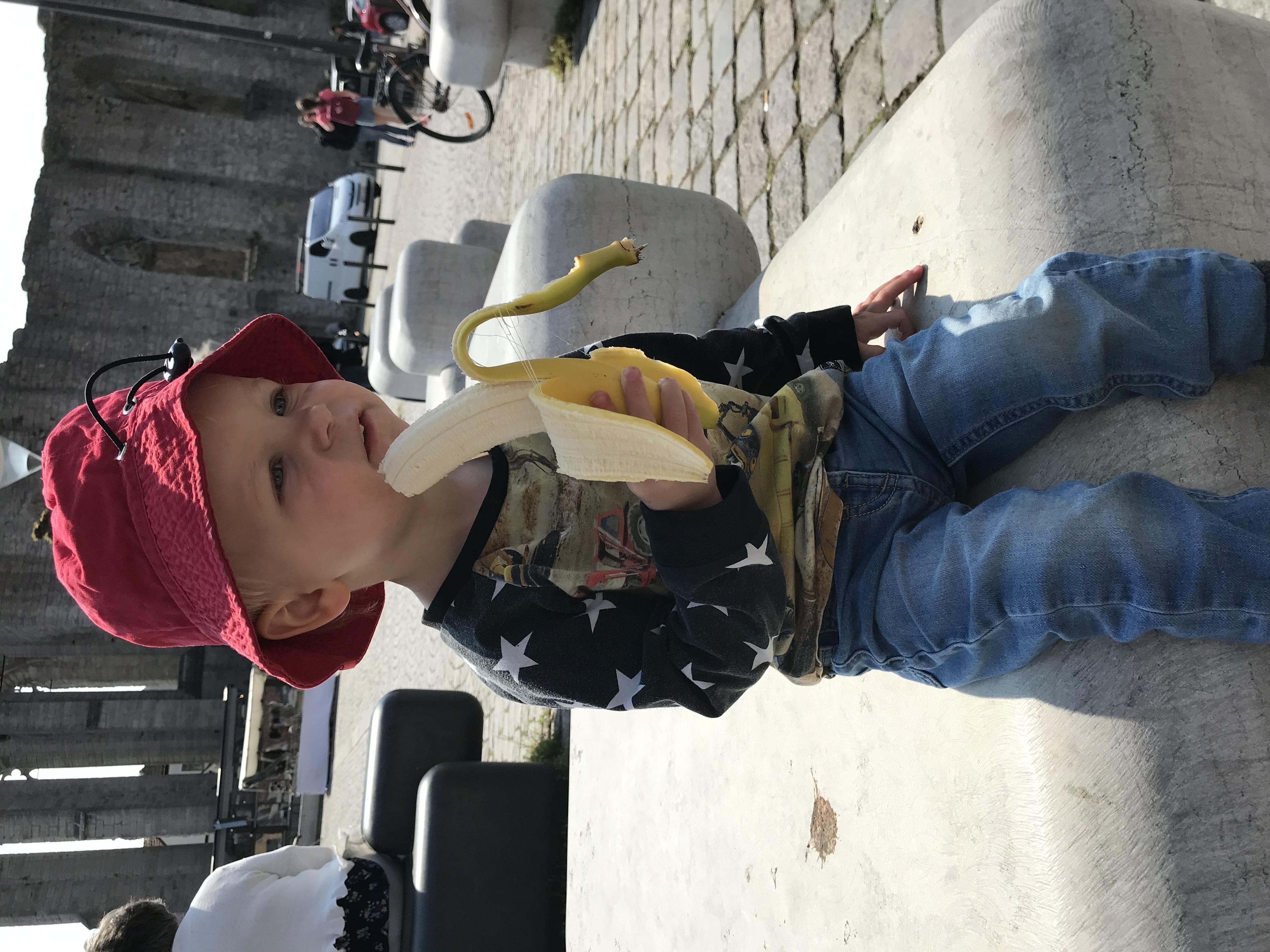 Lillebror jr. äter banan i solhatt